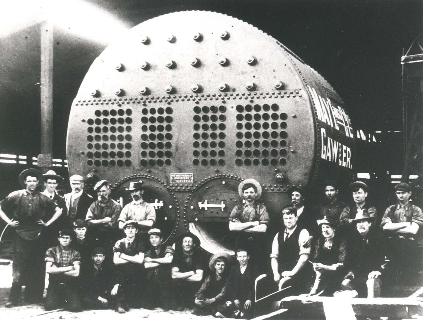 Black and white photo of a group shot of men standing in front of a large cylinder with 'Gawler' printed on the side.