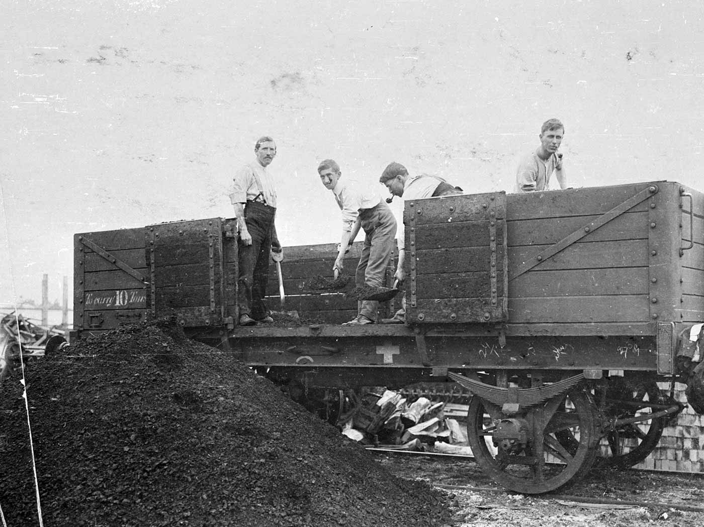 Men unloading coal from a railway wagon.