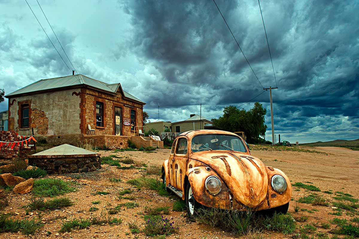 A photograph depicting the theme desert colours and features a rusty, dirty Volkswagen surrounded by dirt and tufts of green grass and a sky filled with grey clouds with a building in the background. - click to view larger image