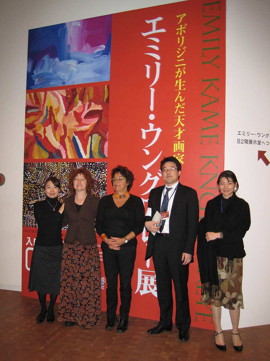 A group of women and a man standing in front of a large exhibition banner. - click to view larger image