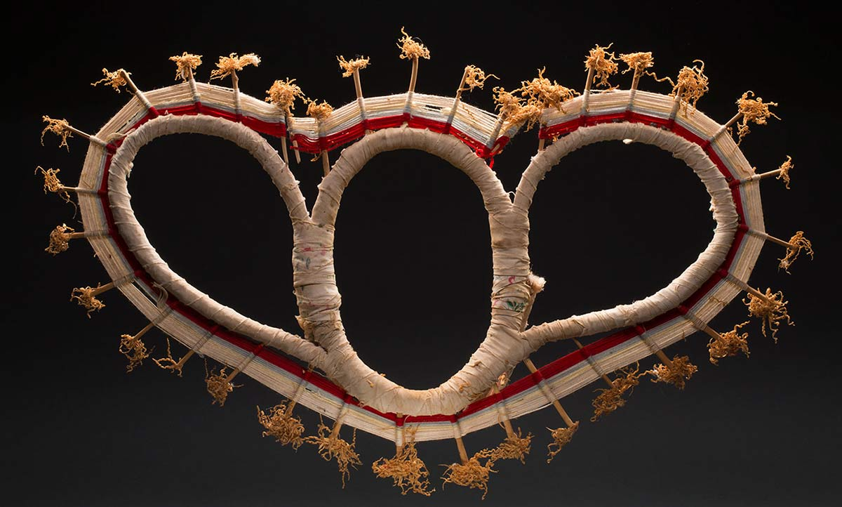 A headdress with a central oval shape and elongated ovals on either side, decorated with red and yellow yarn, with wing shaped appendages (butterfly shape) on either side.