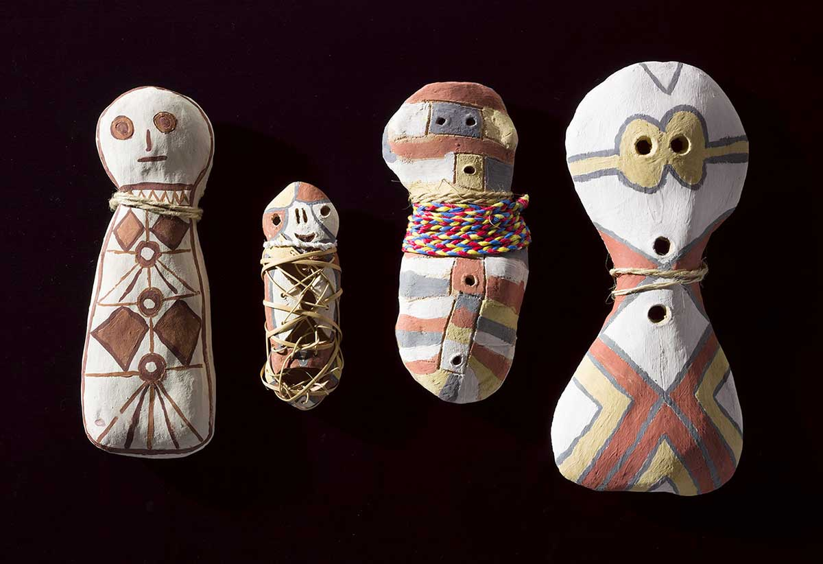 Four clay figures with fibre string adornments and painted surfaces. - click to view larger image