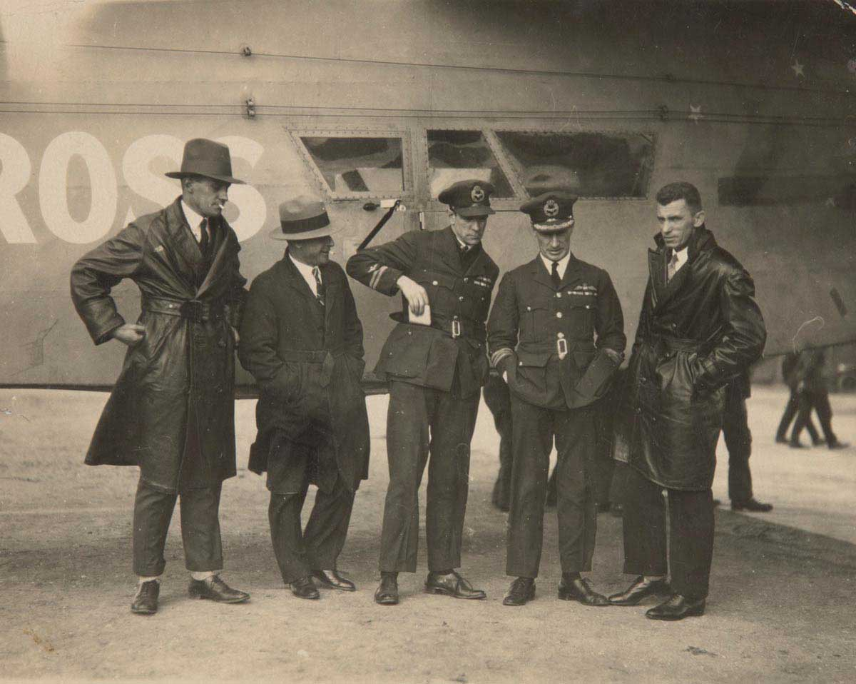 Photo of five men standing in front of an aeroplane.