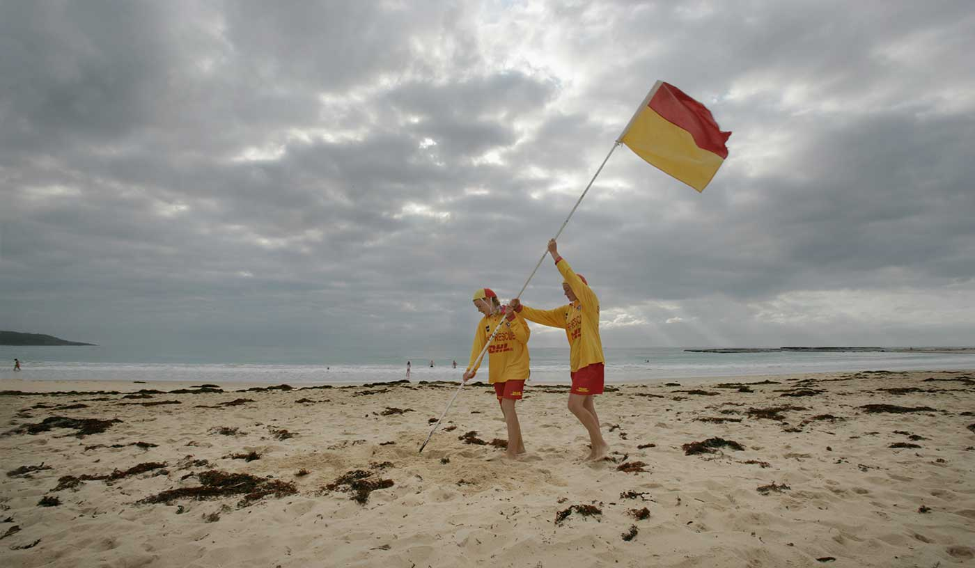 Two surf lifesavers putting a red and yellow flag on the beach at Mollymook, New South Wales, 2006.