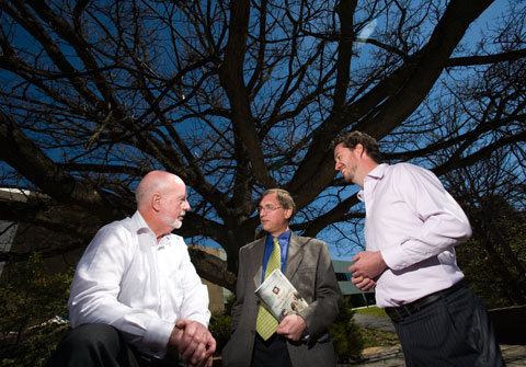 A colour photograph showing three men talking together under a bare branch winter tree with a dark blue evening sky in the background. The man in the middle, Peter Stanley, holds his book under his arm.