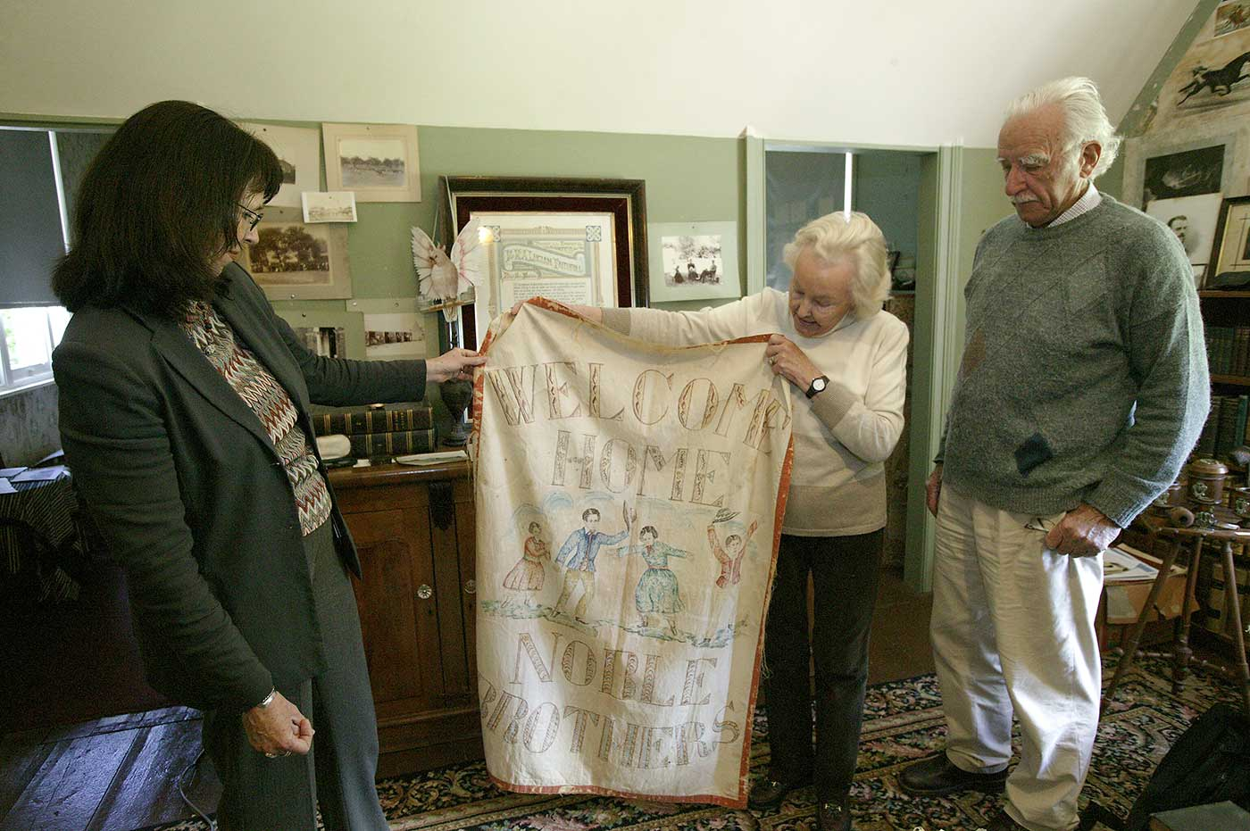 A colour photograph of Pamela and Jim Maple-Brown inside the Faithfull family museum with Carol Cooper from the National Museum of Australia.
