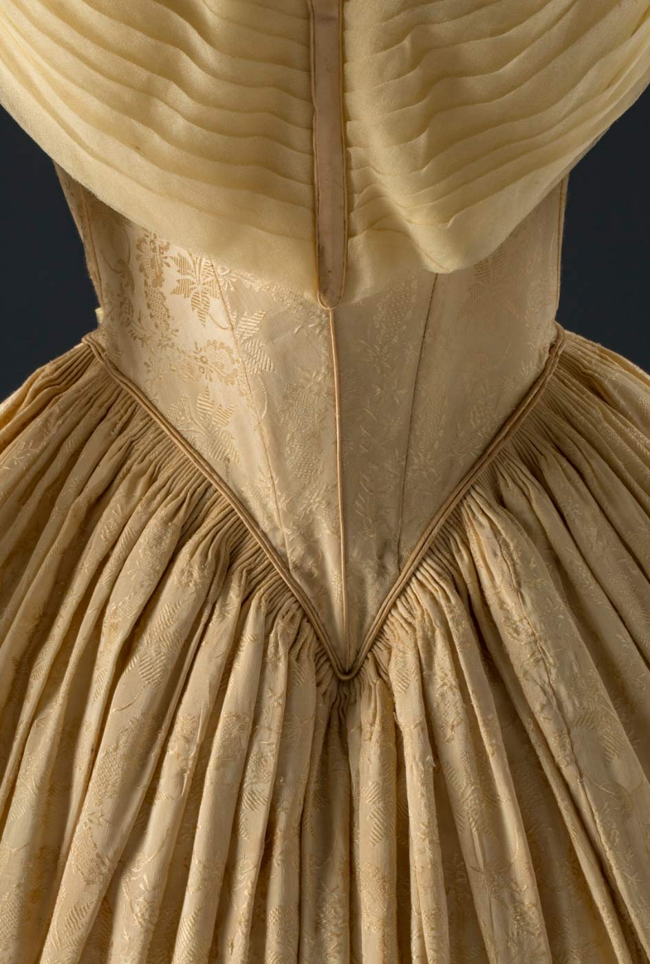 Cropped image of a silk dress with an intricate pattern and detail. - click to view larger image