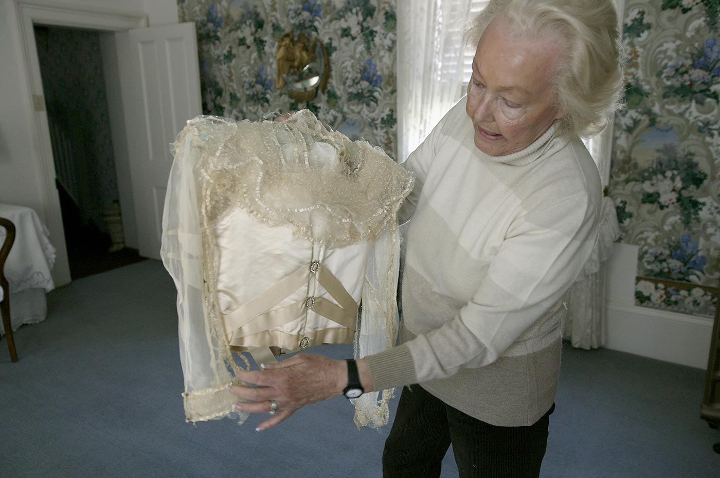 A woman stands in room holding and inspecting the back of a wedding dress bodice.