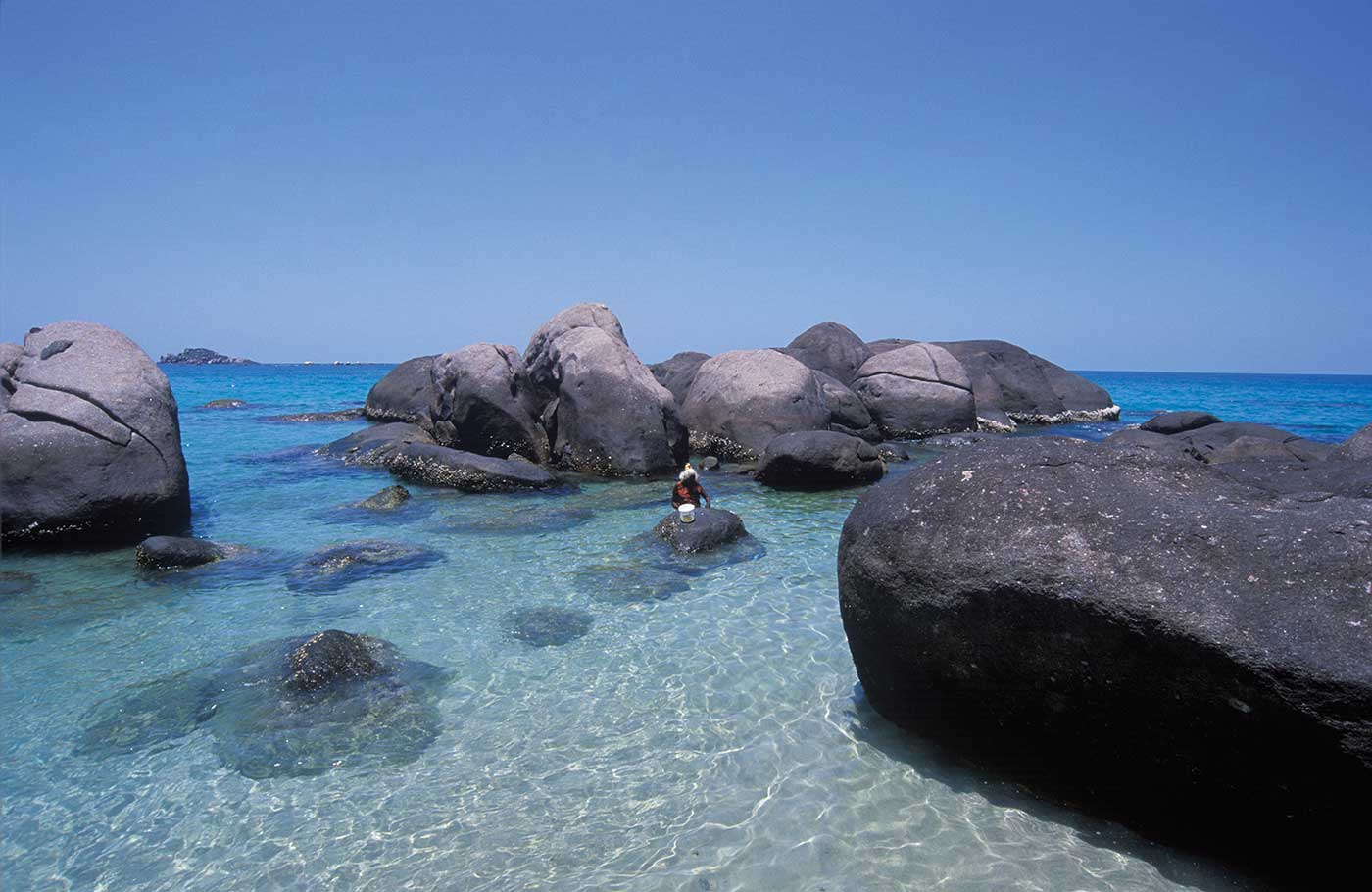 A colour photograph of a person wading in shallow water near a beach. Large rounded boulders surround the person. Submerged rocks can be seen in the clear blue water. Parts of the horizon are visible beyond the large boulders. The blue cloudless sky is in the top half of the photograph.