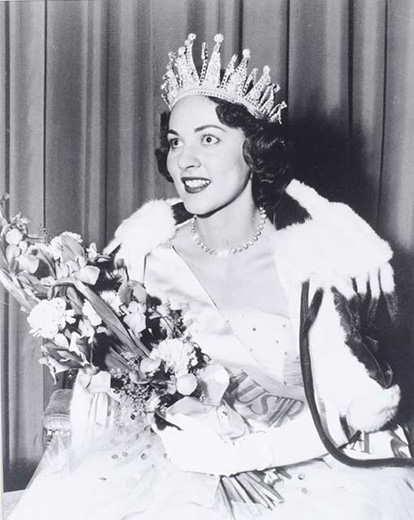 Miss Australia 1958, Pamela McKay holding a bouquet of flowers, wearing the crown and robe and white gloves - click to view larger image
