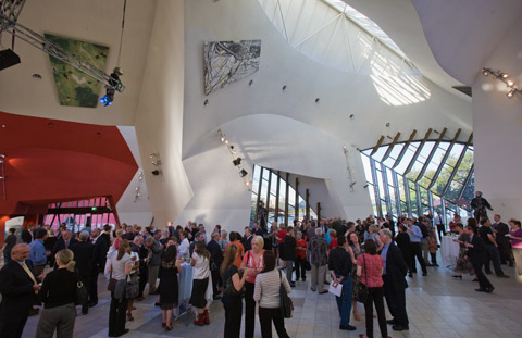 A large group of people in a museum. The group is scattered about an open space. Above them part of the museum's ceiling is visible; it has dramatic curves and two paintings mounted on it. A range of shadows play across the ceiling as it is bathed in both natural and artificial light. In the background are two large curved windows that have reinforcing beams overlaying the glass. The ceiling is a muted white while part of the wall in the left background is red.
