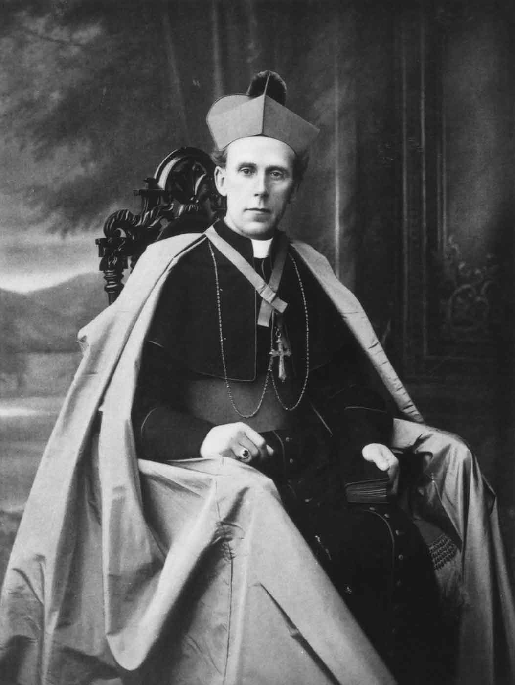 Black and white portrait of a man sitting in an ornate chair and wearing archdiocese attire. - click to view larger image