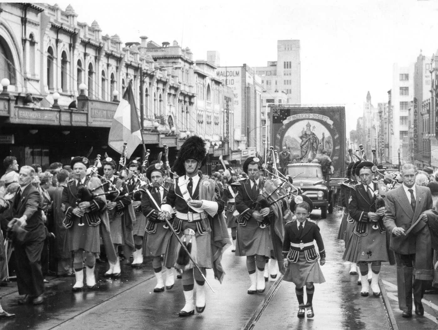 Black and white photo of a procession of bag pipe players walking down a city street with crowds looking on.