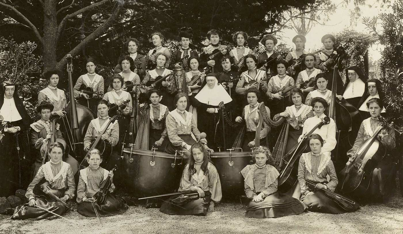 Black and white photo of an orchestra of women and four nuns.