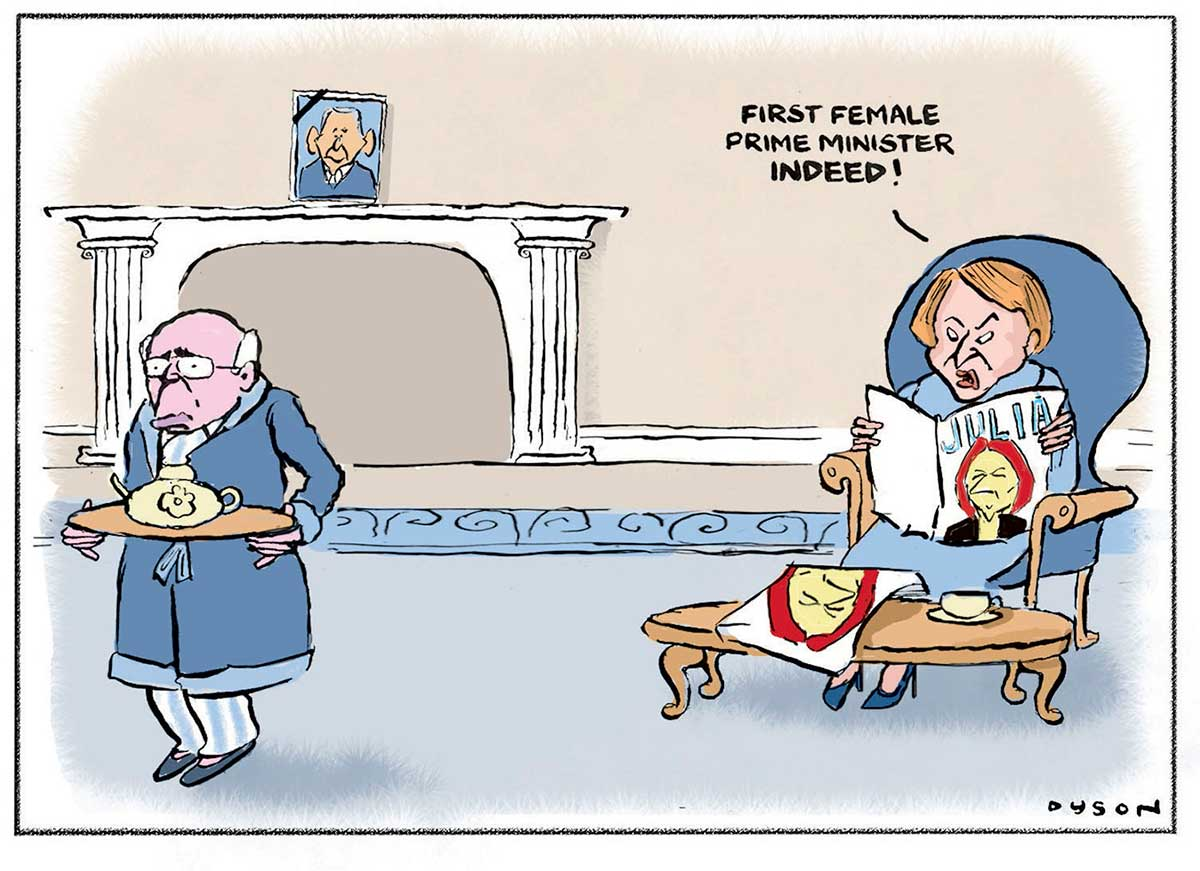 A colour cartoon depicting John and Janette Howard at home. He is at the left of the cartoon, wearing pyjamas and a dressing gown and carrying a platter with a teapot on it. He has a downtrodden expression on his face. She is sitting at the right of the cartoon in a large blue chair reading a magazine with an image of Julia Gillard on the front. She has a look of annoyance on her face and is saying 'First female prime minister indeed!' In the background is a fireplace with a picture of George W Bush above it.  - click to view larger image
