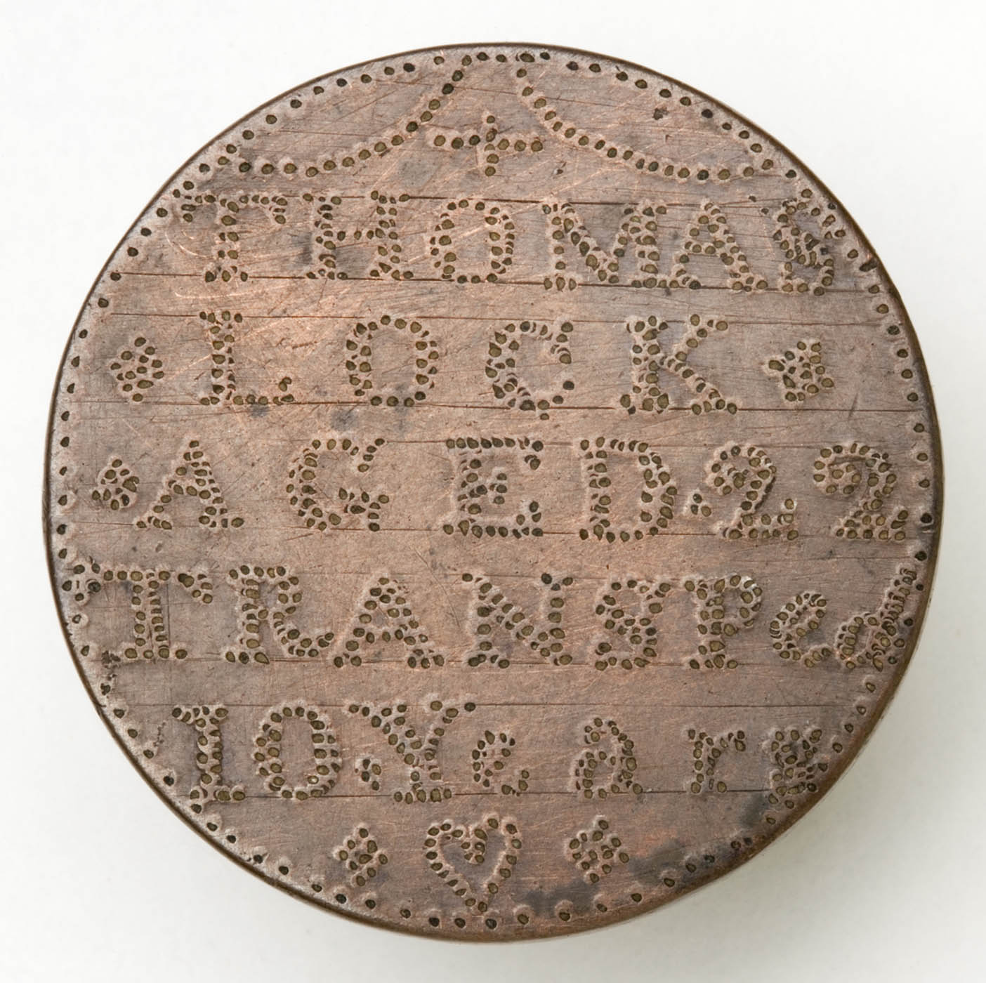 Rusty looking token with embossed letters.
