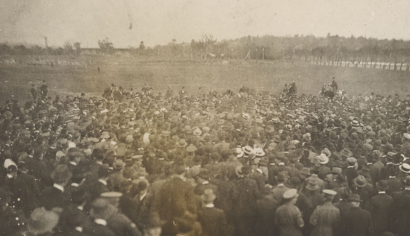 Black and white photo of a huge crowd of people in a field.