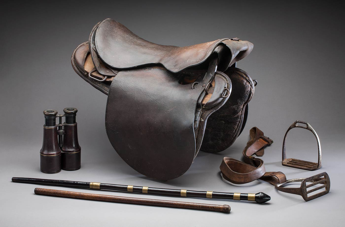 Leather saddle beside a small pair of binoculars and horse stirrups.