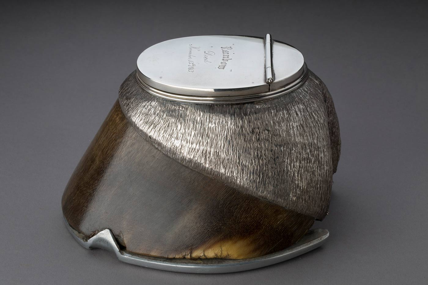Detail of the inscription 'Rainbow died November 13th 1913' on a silver inkwell set into a horse's hoof.