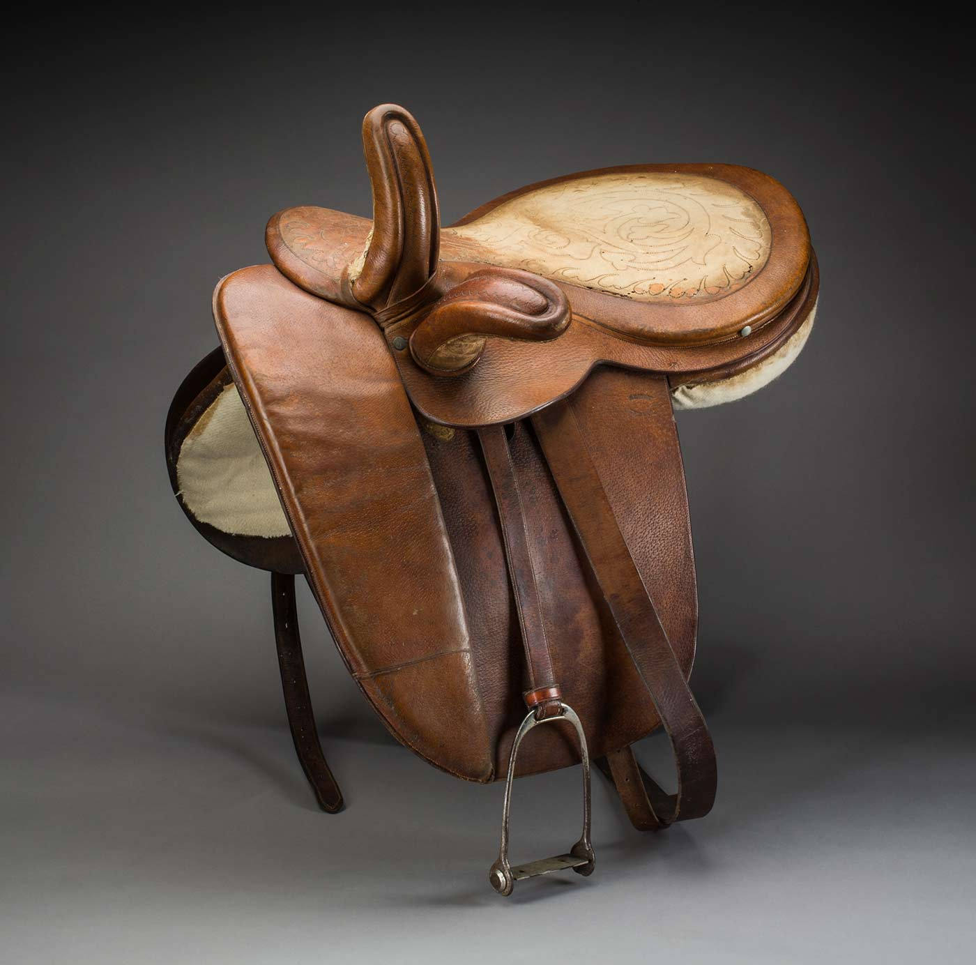 A leather side-saddle, with a pattern tooled into the seat.