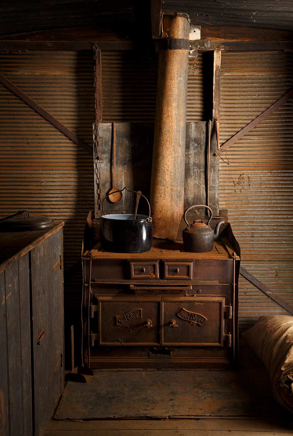 A cook's galley in the form of a metal-clad, timber and iron-framed box raised on wagon wheels. This view is of the wood-fired stove with pan and kettle seated on top. - click to view larger image