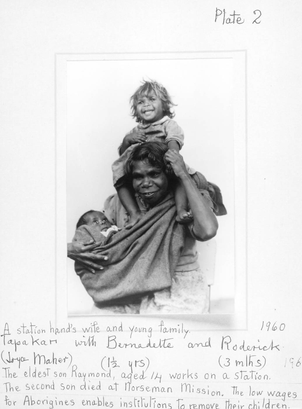 Black and white image of a photo of a woman holding a baby in swaddling and a young girl on her shoulders. Underneath is hand writing describing 'A station hand's wife and young family'. - click to view larger image