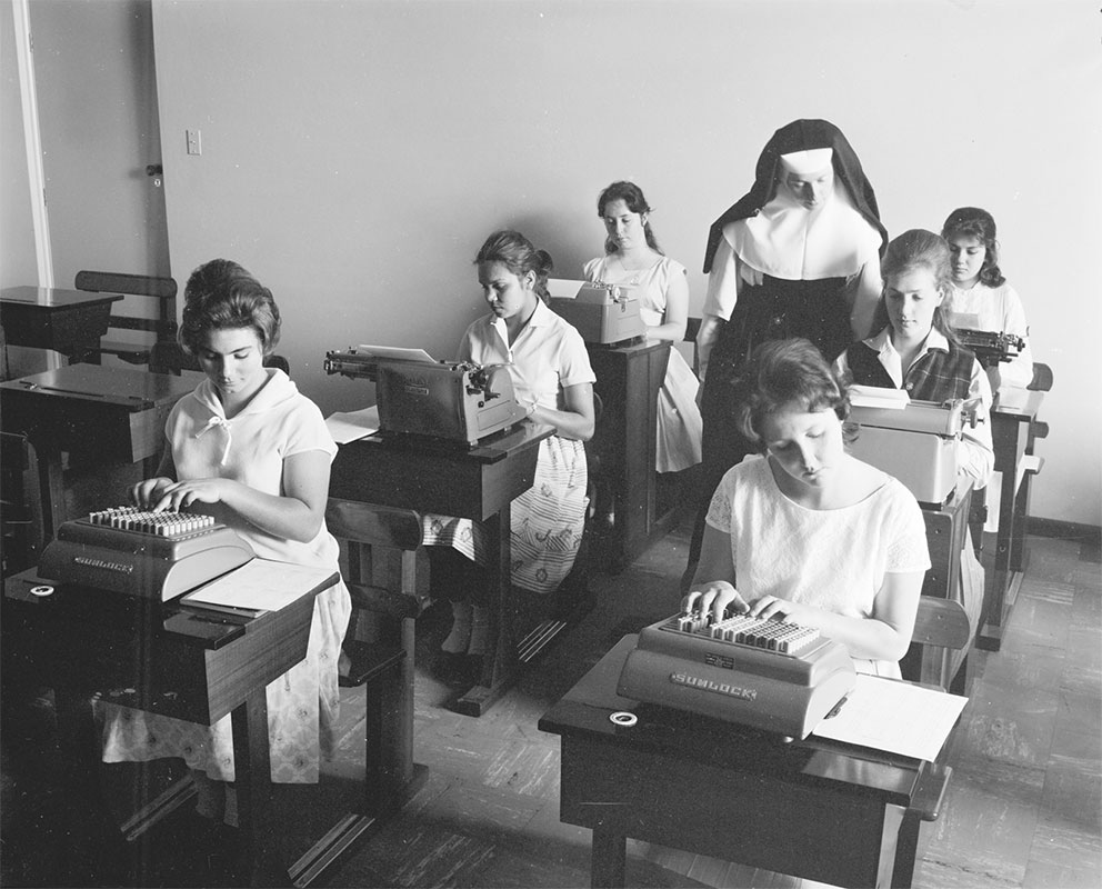 A black and white photograph of six girls sitting at small school desks using tabulating machines and typewriters. They are seated in two rows with some empty desks visible on the left.  The girls at the front of each row are working on tabulating machines and the remaining four are using typewriters. Some girls are wearing short-sleeved dresses and other short-sleeved blouses and skirts. A nun dressed in the traditional nun's black and white habit is standing between the two occupied rows of desks looking down at the work of one of the girls. - click to view larger image