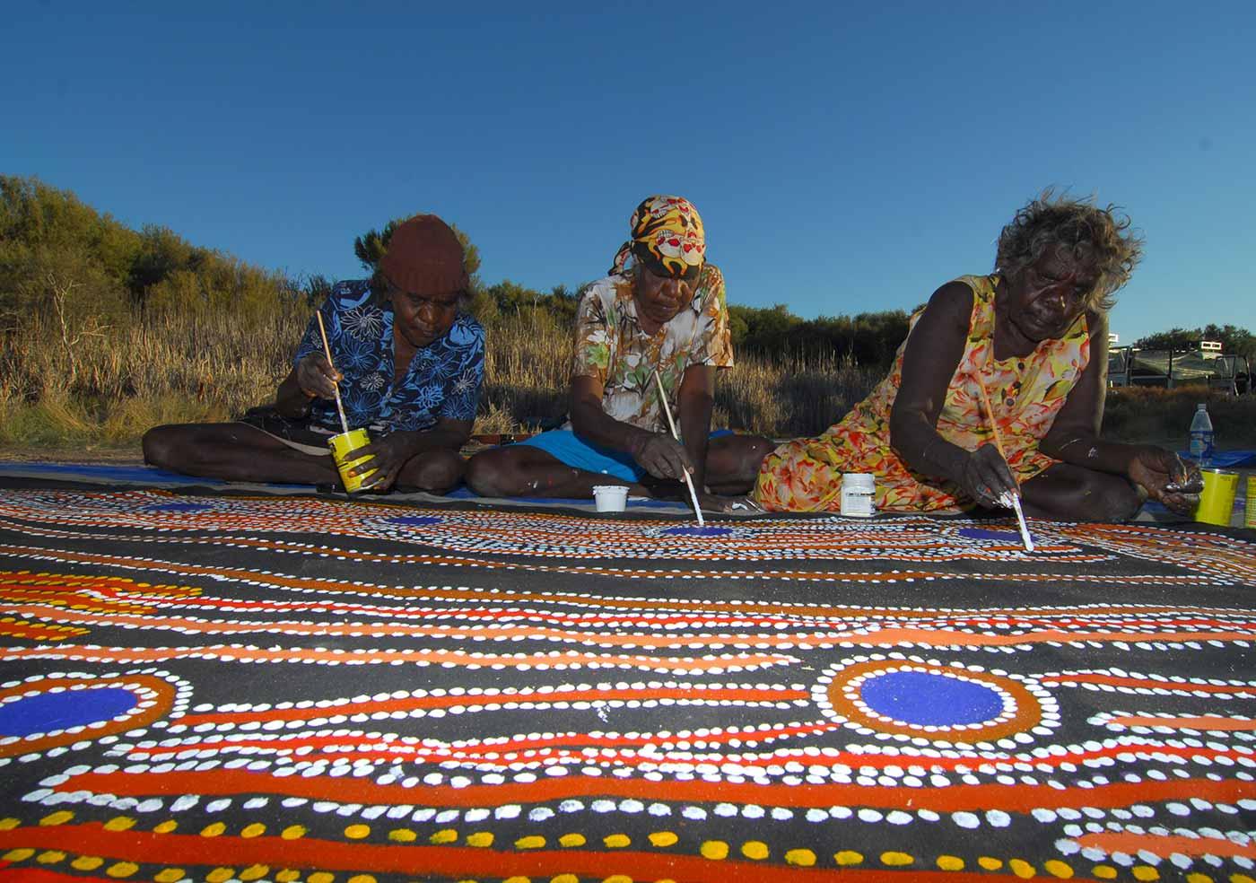 (left to right) Rosie Williams, Dulcie Gibbs and Muni Rita Simpson, from Martumili Artists, working on Minyipuru (Seven Sisters).