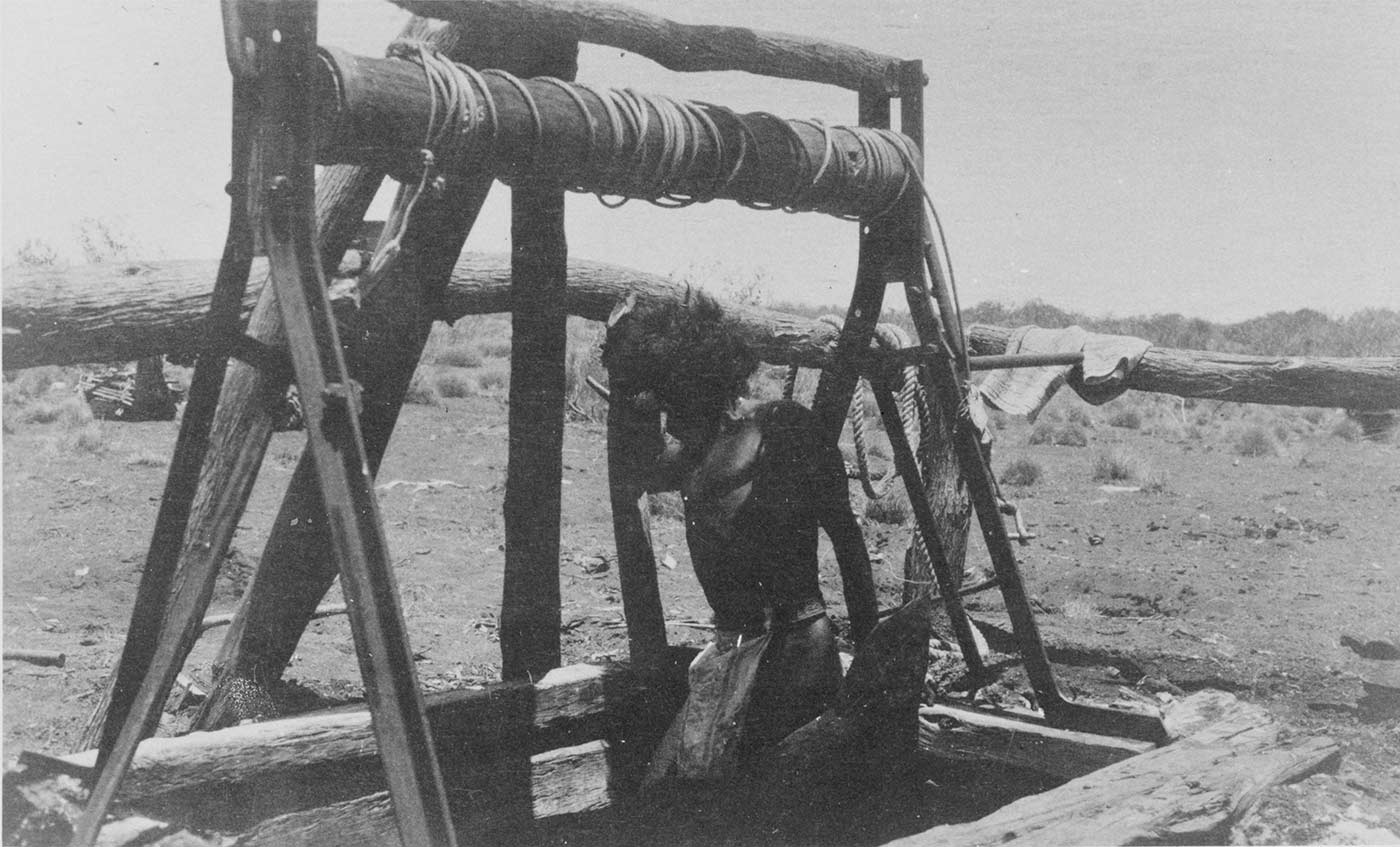 Black and white photo of a man descending or ascending into a well in the ground.