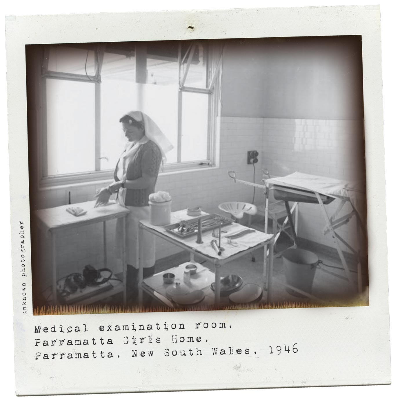 A black and white Polaroid photograph of a medical examination room.  In the room which has tiled walls and a large window there is a nurse, two medical equipment trolleys and an empty patient trolley. The nurse, in uniform and veil, is standing at one of the equipment trolleys and putting on a pair of gloves.  The other equipment trolley is laid out with medical instruments, swabs and dishes. There is a stool on wheels at the end of the patient trolley. The patient trolley has a bucket underneath it.  Typewritten text underneath the photograph reads: 'Medical examination room. Parramatta Girls Home. Parramatta. New South Wales, 1946'. Smaller text, on the left-hand side of the image, in a vertical direction, reads 'Unknown photographer'. - click to view larger image