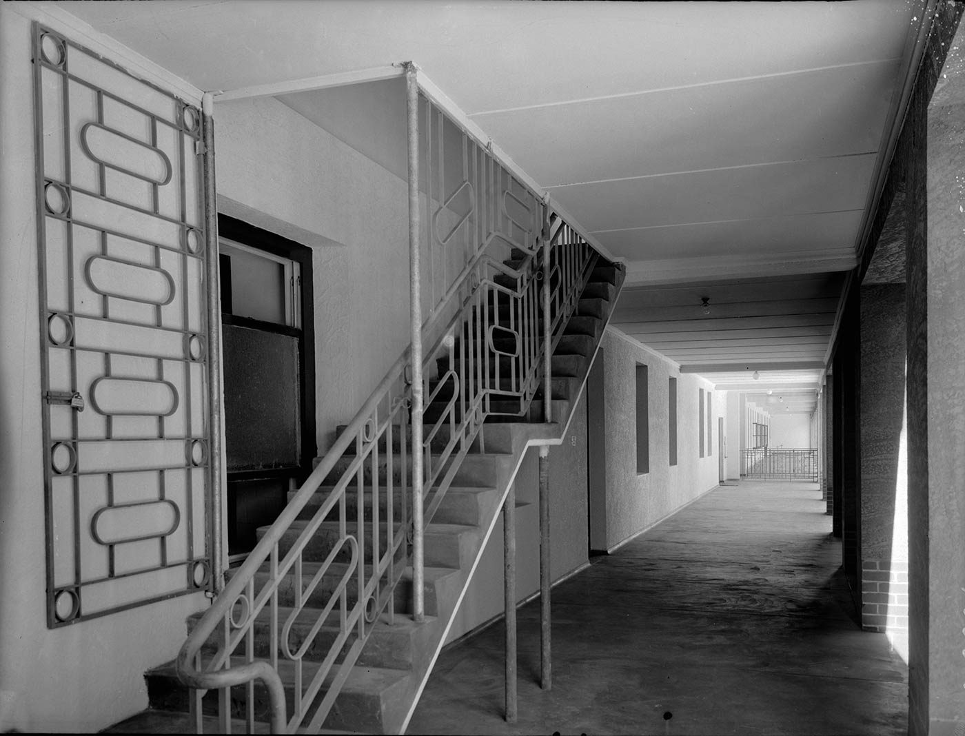 Black and white photo showing concrete stairs on an external verandah. The stairs have an ironwork rail, and a panel of ironwork is also mounted on the wall of the building. - click to view larger image