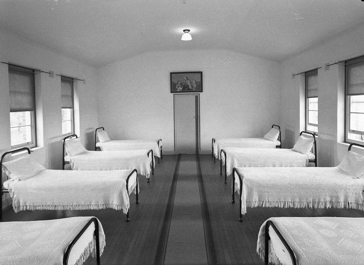 Black and white image showing two rows of single beds on either side of a room. The room has floorboards and a central runner leading to a door at the far end. - click to view larger image