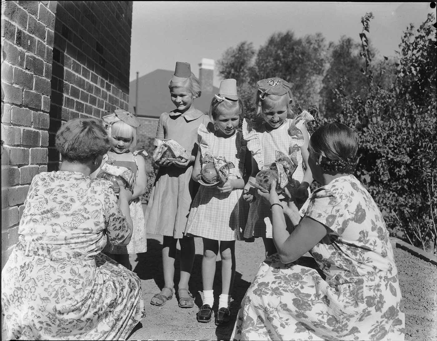 Black and white photo showing four young girls, wearing dresses and party hats, receiving gifts from two women, who kneel in front of the girls, with their backs to the camera. - click to view larger image