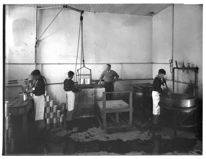 Black and white photo showing three boys in white aprons, working in a large room, under the supervision of a male adult. The boy on the far right uses a pole to stir a large vat, the boy on the left stands at a table working on a tin, and the boy at the centre moves two tins using a pulley. - click to view larger image