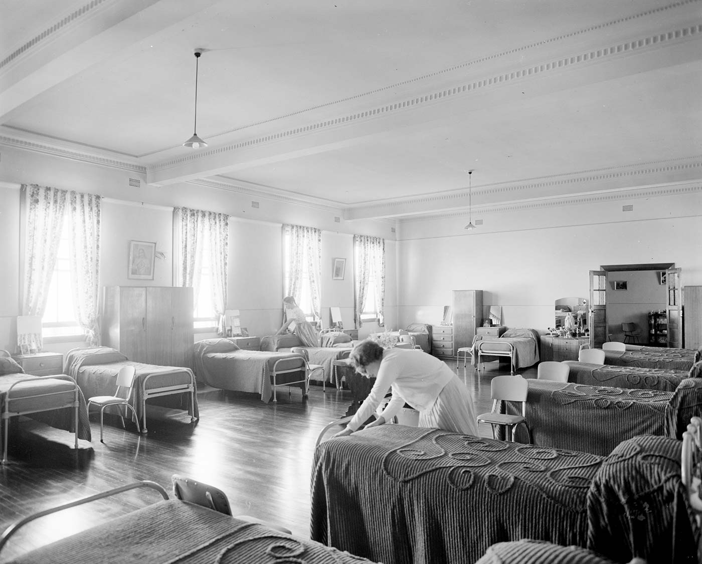 Black and white image showing a light, airy room with two rows of narrow, single beds along either side. A woman leans over a bed in the forground, to tuck in a bedspread. - click to view larger image