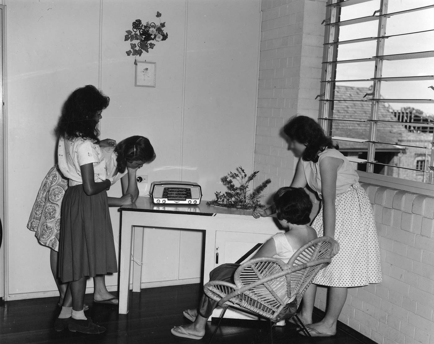 Black and white photo showing four teenage girls gathered around a small radio which sits on a table. Three of the girls are standing, one sits in a low chair. - click to view larger image
