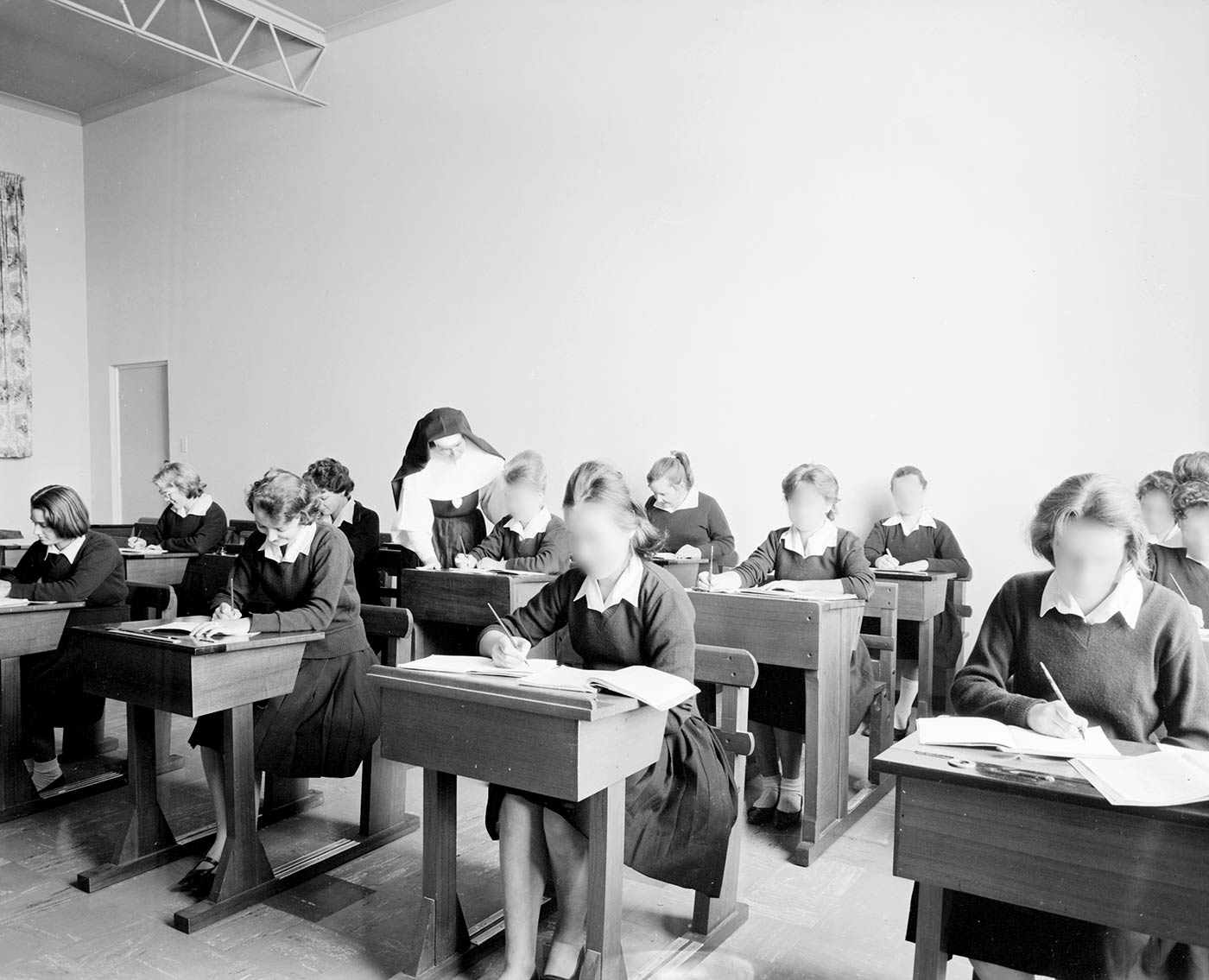 Black and white photo showing 12 teenage girls sitting at wooden desks, writing in exercise books. A nun wearing a dark habit and veil leans over one of the desks. - click to view larger image