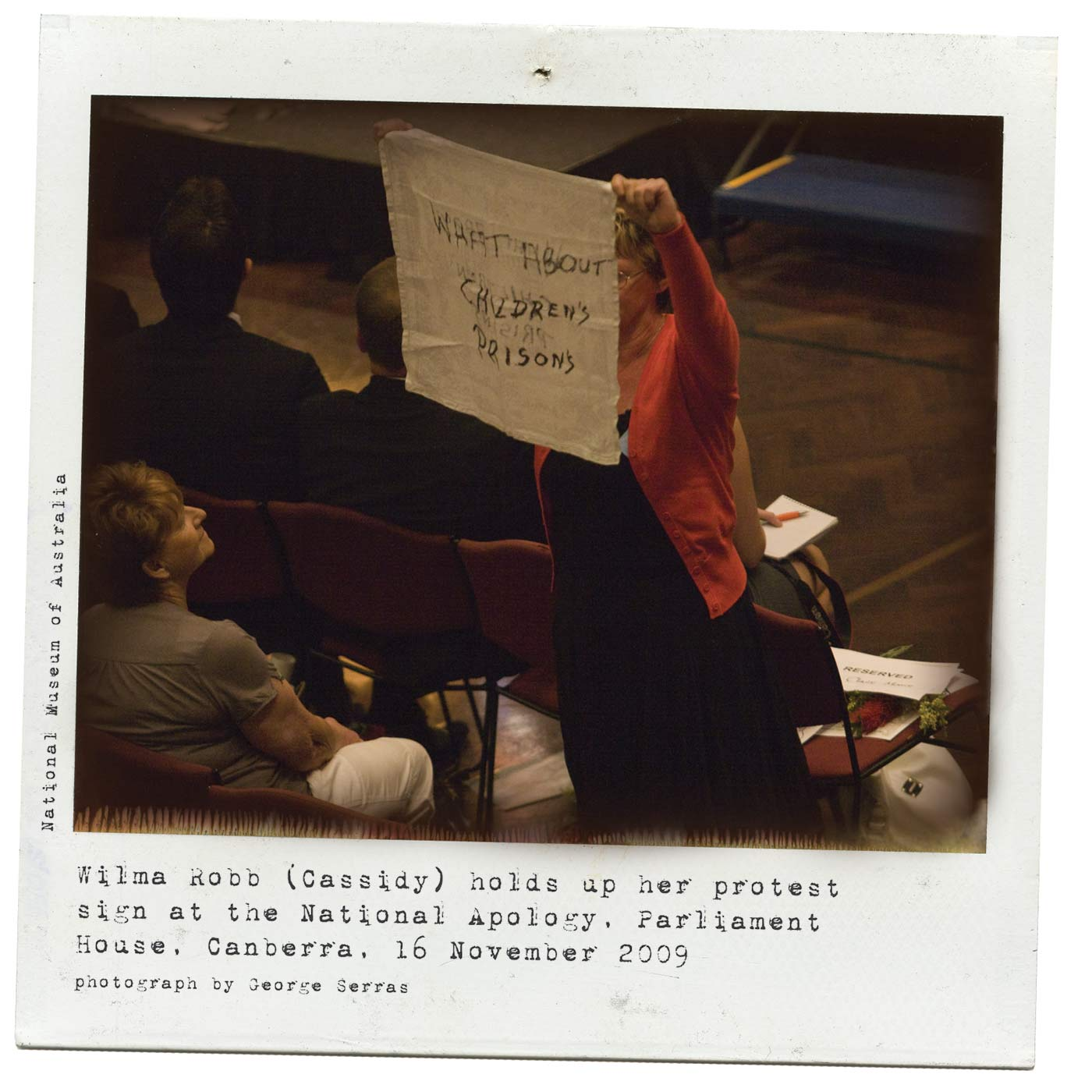 A colour Polaroid photo of a woman, standing and holding a white piece of fabric in raised arms. 'WHAT ABOUT CHILDREN'S PRISONS' is written on the fabric in black texta. Typewritten text below reads 'Wilma Robb )Cassidy) holds up her protest sign at the National Apology, Parliament House, Canberra, 16 November 2009. Photograph by George Serras'. - click to view larger image