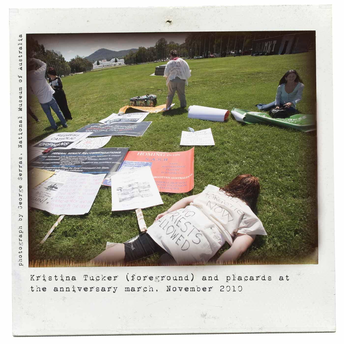 Polaroid photo showing protesters, with Old Parliament House and Mount Ainslie in the distance. In the foreground, a woman lies face down on the grass, wearing a white T-shirt covered with handwritten text 'NO PRIESTS ALLOWED'. Various protest banners are laid on the grass, and four people can be seen in the middle distance. One of them also wears a white T-shirt with writing on it. Typewritten text under the photo reads 'Kristina Tucker (foreground) and placards at the anniversary march, November 2010'. 'Photograph by George Serras, National Museum of Australia' is printed on the left side. - click to view larger image