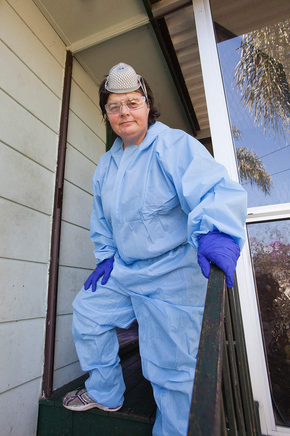 Colour photograph of a woman in a sky blue coverall, wearing blue gloves, safety glasses, and with a gas mask resting on her head. - click to view larger image