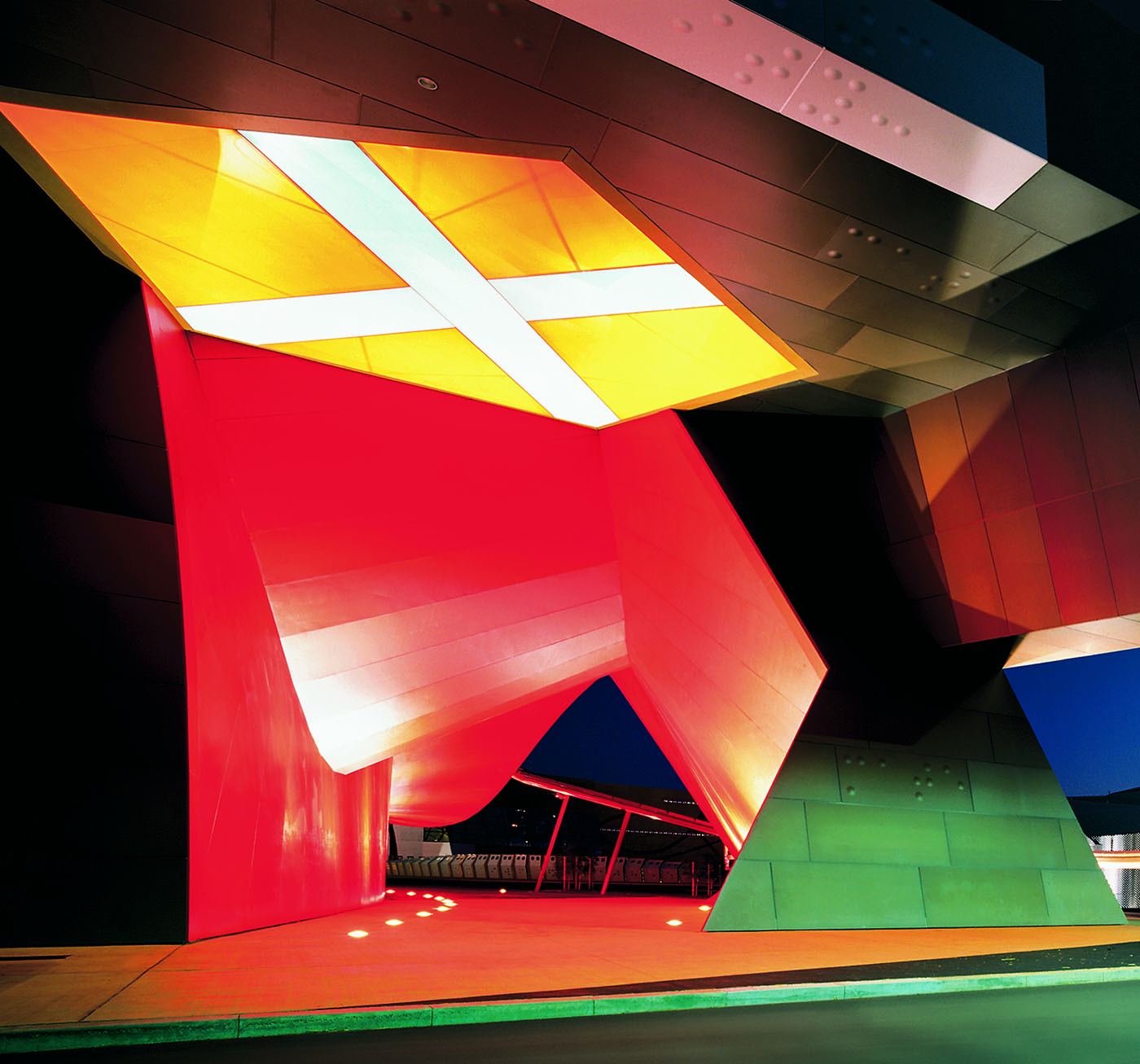Exterior of a building, illuminated at night. A large, white cross on an orange background rises above a red curved wall.