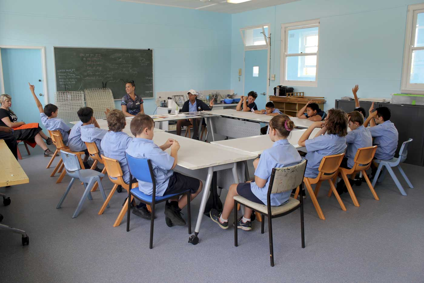 Primary school students and a female teacher are sitting around desks and having a discussion. - click to view larger image