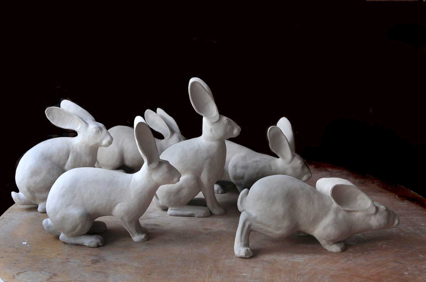 Six matt white ceramic figures modelled on the European wild rabbit.