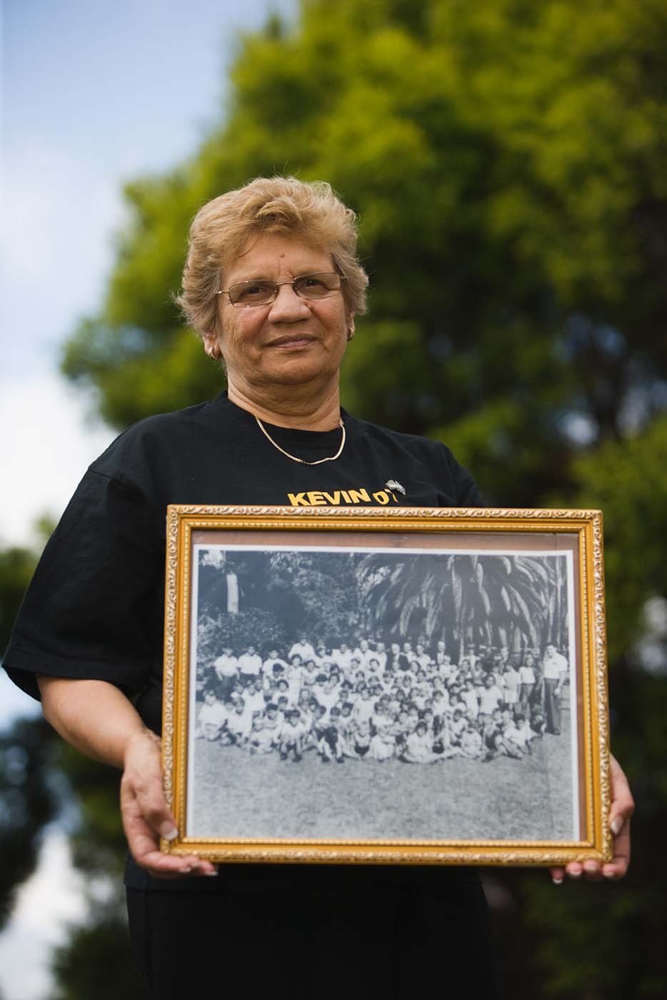 Mary Terszak holding a photograph of herself with her school mates. - click to view larger image