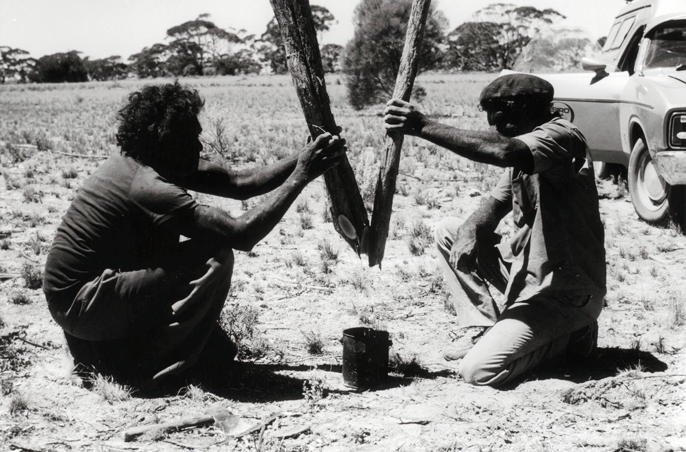 Black and white image showing side view of two men, squatting on the ground and holding sections of tree branches above a small tin.