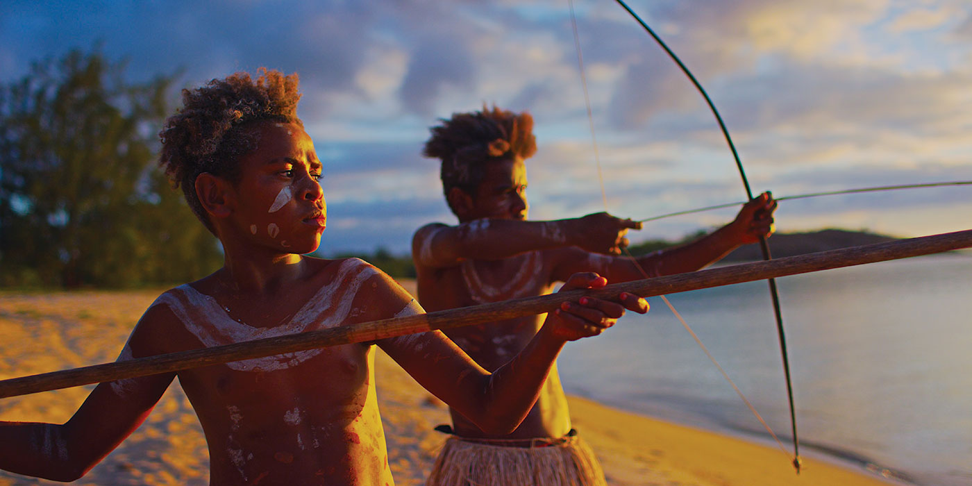 Two young boys are standing on a beach with spear and bow and arrow raised in attack mode.