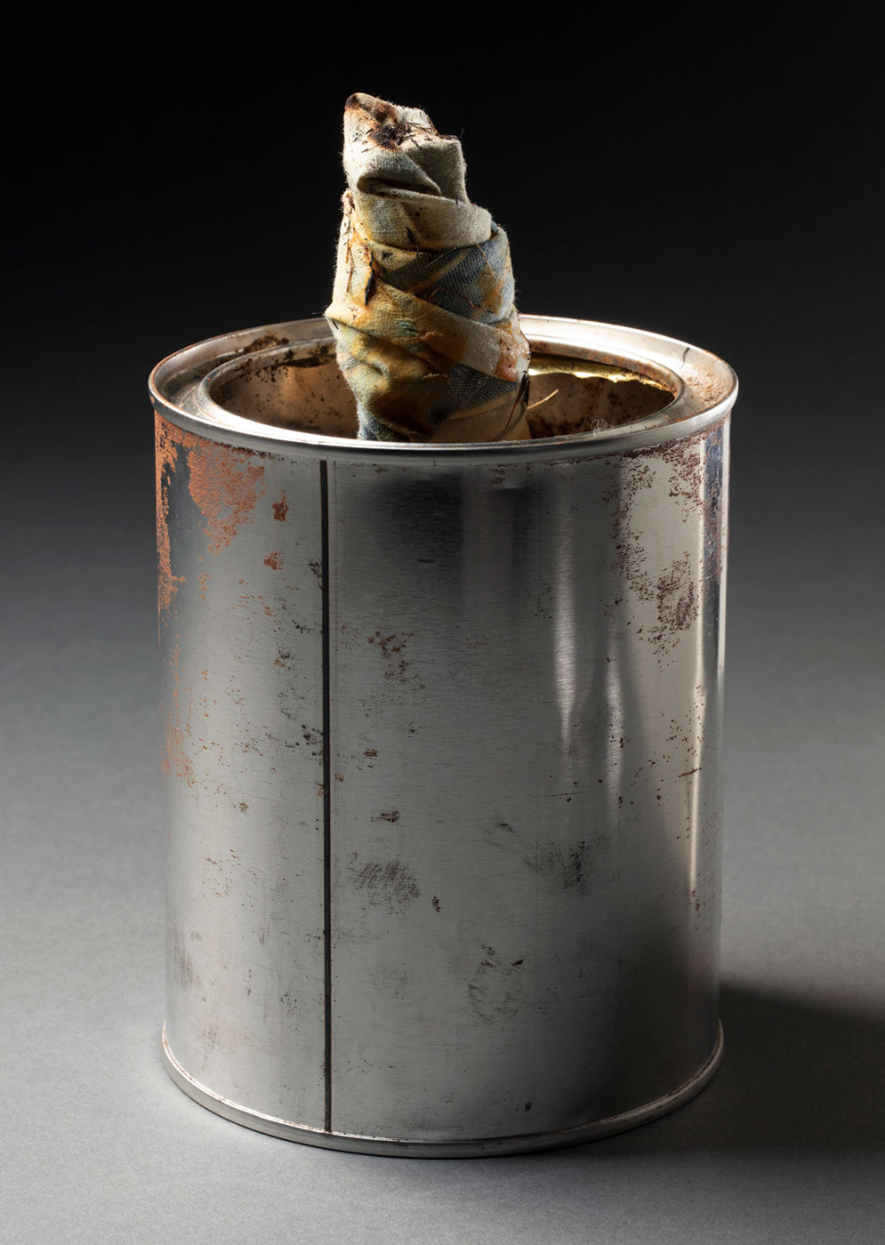 Lamp consisting of a metal tin holding a wick made from a twisted piece of blue and fabric . - click to view larger image