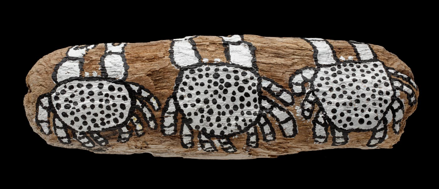 An acrylic painting on driftwood featuring three white crabs with a black outline and dots. - click to view larger image