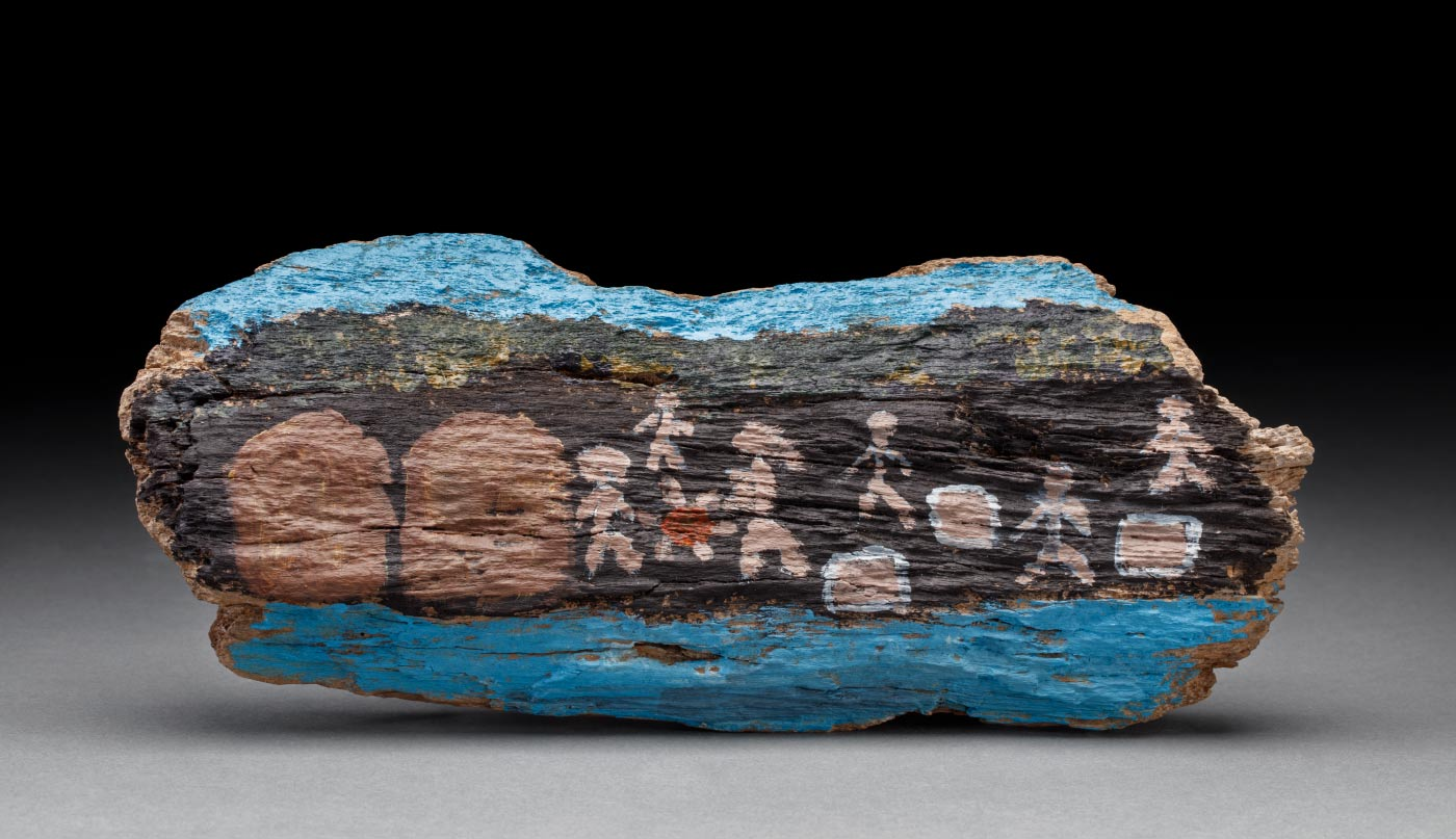An acrylic painting on driftwood featuring a blue stripe across the top and bottom of the wood and stick figures amongst other forms across the centre. - click to view larger image