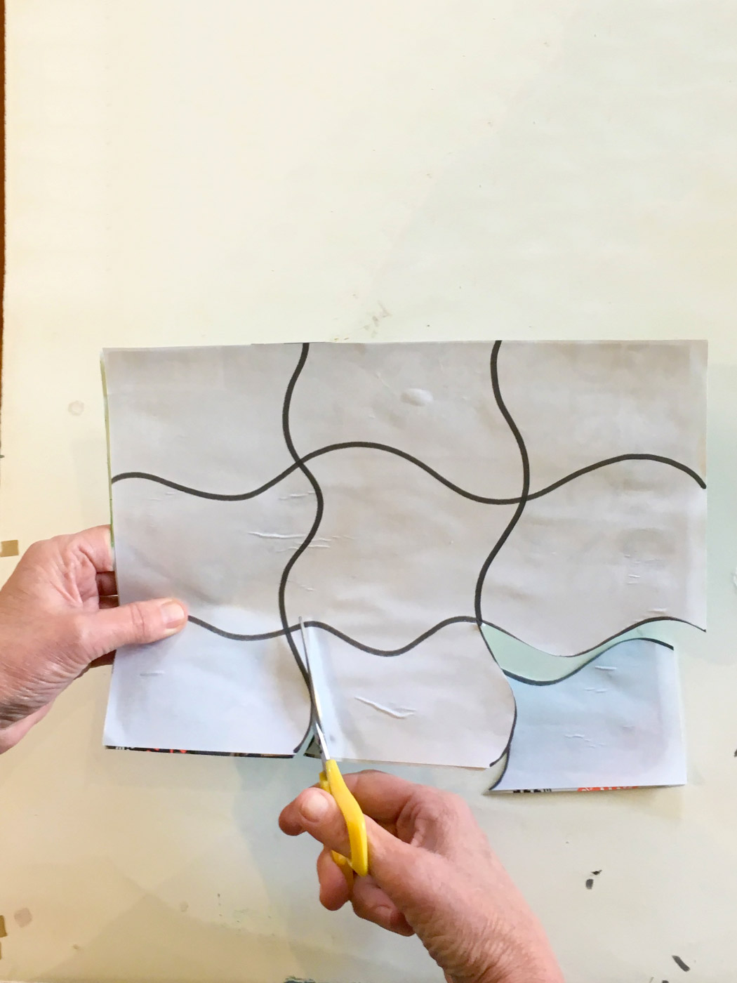 A pair of hands cutting along the lines of a template for a jigsaw puzzle.